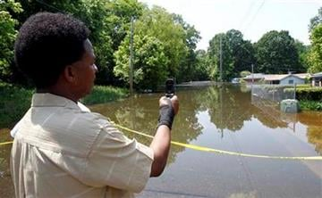 Cedric Briggs takes a photo with his phone in the Box Town neighborhood Sunday, May 8, 2011 in Memphis, Tenn. as flood waters continue to rise along the Mississippi River. (AP Photo/Wade Payne) By Wade Payne