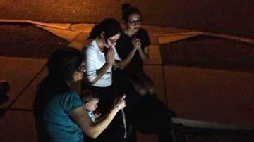 Three women pray the Rosary at Mother of Mercy Mission Catholic Church in Phoenix after a priest was found dead and another badly injured. (Source: CBS 5 News) By Brendan Marks