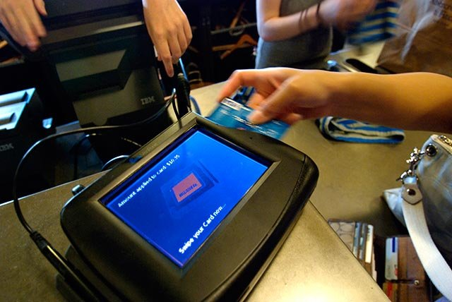 An unidentified shopper swipes a credit card to make a purchase. (AP IMages)