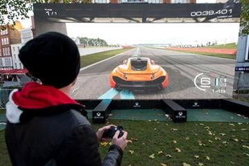 """A man plays the """"Forza 5"""" driving game on a massive screen at a launch party for the new Microsoft Xbox One console in central London on November 21, 2013.  PHOTO / LEON NEAL        (Photo credit should read LEON NEAL/AFP/Getty Images) By LEON NEAL"""