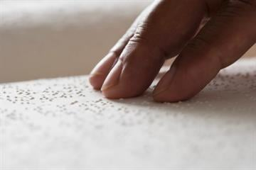 Close up of hand reading Braille By Blend Images - JGI