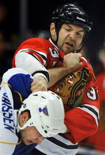 Chicago Blackhawks' John Scott top, fights with St. Louis Blues' Cam Janssen in the first period of an NHL hockey game in Chicago, Tuesday, Nov. 30, 2010. Chicago won 7-5. (AP Photo/Paul Beaty) By Paul Beaty