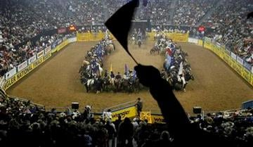 A fan waves a flag before the start of the first go-round of 52nd annual National Finals Rodeo Thursday, Dec. 2, 2010, in Las Vegas. (AP Photo/Isaac Brekken) By Isaac Brekken