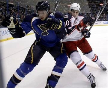 St. Louis Blues' Erik Johnson, left, is checked into the boards by Columbus Blue Jackets' Jared Boll during the first period of an NHL hockey game Thursday, Dec. 9, 2010, in St. Louis. (AP Photo/Jeff Roberson) By Jeff Roberson