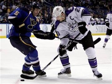 Los Angeles Kings' Dustin Brown, right, controls the puck as St. Louis Blues' Barret Jackman defends during the first period of an NHL hockey game, Thursday, Dec. 16, 2010, in St. Louis. (AP Photo/Jeff Roberson) By Jeff Roberson
