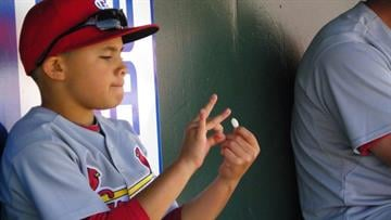 Albert Pujols' son, A.J., flicks sunflower seeds in the dugout during Friday's game between the Marlins and the Cardinals. By Lakisha Jackson
