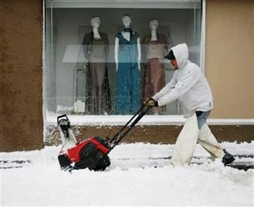 Toby Sumner, of Ritzman Lawn Service, clears snow in front of a Weaver's Department Store window Saturday, March 20, 2010, in Lawrence, Kan. (AP Photo/Orlin Wagner) By Orlin Wagner