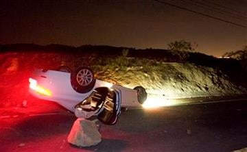 A car sits rolled over in the wake of Friday nights March 28, 2014 earthquake on Carbon Canyon Road in Brea, Calif., near Olinda Village. (AP Photo/The Orange County Register, Rod Veal) By ROD VEAL,