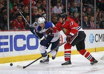 CHICAGO, IL - APRIL 06: Sheldon Brookbank #17 of the Chicago Blackhawks and T.J. Oshie #74 of the St. Louis Blues move to the puck at the United Center on April 6, 2014  in Chicago, Illinois. (Photo by Jonathan Daniel/Getty Images) By Jonathan Daniel