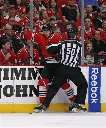CHICAGO, IL - APRIL 06: Bryan Bickell #29 of the Chicago Blackhawks collides with lineman Scott Cherrey #50 against the St. Louis Blues at the United Center on April 6, 2014  in Chicago, Illinois. (Photo by Jonathan Daniel/Getty Images) By Jonathan Daniel