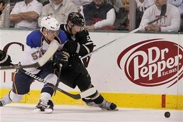 Dallas Stars defenseman Alex Goligoski (33) and St. Louis Blues left wing David Perron (57) battle for control of the puck during the second period of an NHL Hockey game, Saturday, April 7, 2012, in Dallas. (AP Photo/Brandon Wade) By Brandon Wade