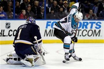San Jose Sharks' Torrey Mitchell, right, tries to control a loose puck as St. Louis Blues goalie Brian Elliott defends during the first period of an NHL hockey game, Saturday, Dec. 10, 2011, in St. Louis. (AP Photo/Jeff Roberson) By Jeff Roberson