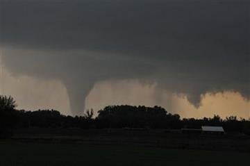 A tornado moves on the ground north of Solomon, Kan., on Saturday evening, April 14, 2012, with I-70 seen in the foreground. (AP Photo/The Hutchinson News, Sandra J. Milburn) By Sandra J. Milburn
