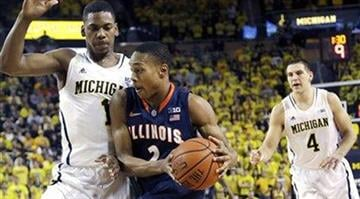 Illinois guard Joseph Bertrand (2) drives to the basket while defended by Michigan forward Glenn Robinson III (1) during the first half of an NCAA college basketball game, Sunday, Feb. 24, 2013 in Ann Arbor, Mich. (AP Photo/Carlos Osorio) By Dan Mueller