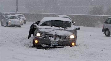 A motorist is helped after encountering a snow drift on Highway 64 in Ladue, Missouri on February 21, 2013. A morning ice storm and then several inches of snow have slowed or closed roads, businesses and schools.      UPI/Bill Greenblatt By Eric Lorenz