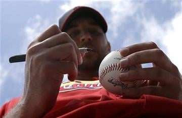 St. Louis Cardinals starting pitcher Adam Wainwright signs a baseball during spring training baseball, Tuesday, Feb. 19, 2013, in Jupiter, Fla. (AP Photo/Julio Cortez) By Julio Cortez
