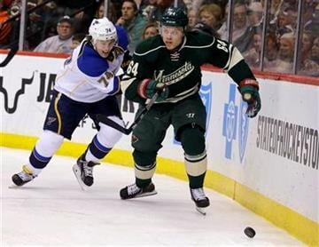 St. Louis Blues right wing T.J. Oshie (74) and Minnesota Wild center Mikael Granlund (64), of Finland, chase the puck during the second period of an NHL hockey game in St. Paul, Minn., Tuesday, Dec. 31, 2013. (AP Photo/Ann Heisenfelt) By Ann Heisenfelt