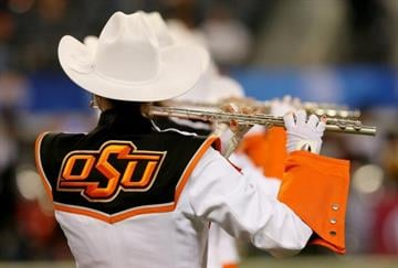 ARLINGTON, TX - JANUARY 03:  A member of the Oklahoma State Cowboys band performs before taking on the Missouri Tigers in the AT&T Cotton Bowl on January 3, 2014 in Arlington, Texas.  (Photo by Ronald Martinez/Getty Images) By Ronald Martinez