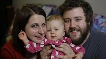 This photo taken Dec. 20, 2013 shows Amanda Leigh Pulte, left, and Matthew Gage, right, posing with their daughter Zoey at their home in Austin. By Brendan Marks