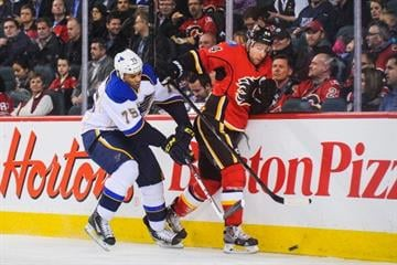 CALGARY, AB - JANUARY 9: Ryan Reaves #75 of the St. Louis Blues checks Chris Butler #44 of the Calgary Flames during an NHL game at Scotiabank Saddledome on January 9, 2014 in Calgary, Alberta, Canada. (Photo by Derek Leung/Getty Images) By Derek Leung