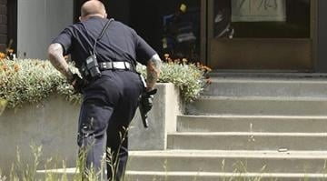 An Oakland police officer approaches the entrance to Oikos University in Oakland, Calif., Monday, April 2, 2012. (AP Photo/Noah Berger) By Belo Content KMOV