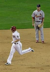 Arizona Diamondbacks' Mark Reynolds, left, rounds the bases after hitting a three-run home run as St. Louis Cardinals' David Freese (23) looks on in the fourth inning of a baseball game Tuesday, April 20, 2010, in Phoenix. By KMOV Web Producer