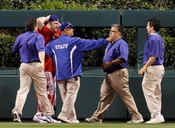 A fan, in red, that ran onto the field is detained by stadium personnel in the ninth inning of a baseball game between the Philadelphia Phillies and the St. Louis Cardinals, Tuesday, May 4, 2010, in Philadelphia. (AP Photo/Matt Slocum) By Matt Slocum