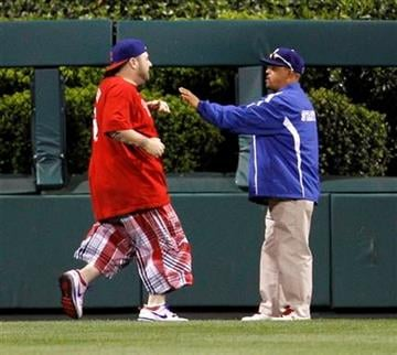A fan, left, that ran onto the field is detained by stadium personnel in the ninth inning of a baseball game between the Philadelphia Phillies and the St. Louis Cardinals, Tuesday, May 4, 2010, in Philadelphia. (AP Photo/Matt Slocum) By Matt Slocum