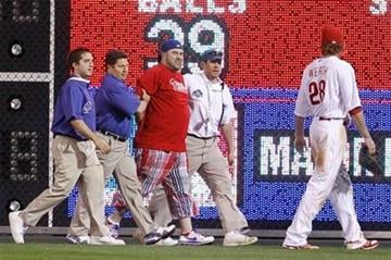 Stadium personnel detain a fan that ran onto the field as Philadelphia Phillies' Jayson Werth looks on in the ninth inning of a baseball game against the St. Louis Cardinals, Tuesday, May 4, 2010, in Philadelphia. (AP Photo/Matt Slocum) By Matt Slocum