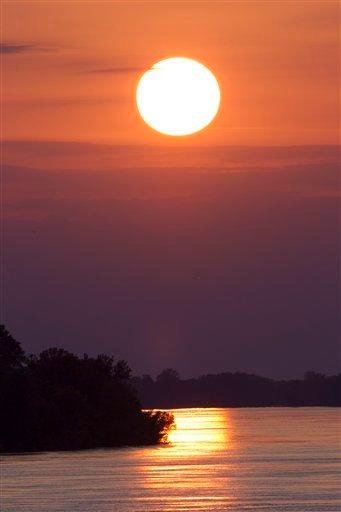 The sun sets over the flooding Mississippi river in Vicksburg, Miss., Wednesday, May 18,  2011.  Floodwaters from the Mississippi river are expected to crest in Vicksburg on Thursday. (AP Photo/Dave Martin) By Dave Martin
