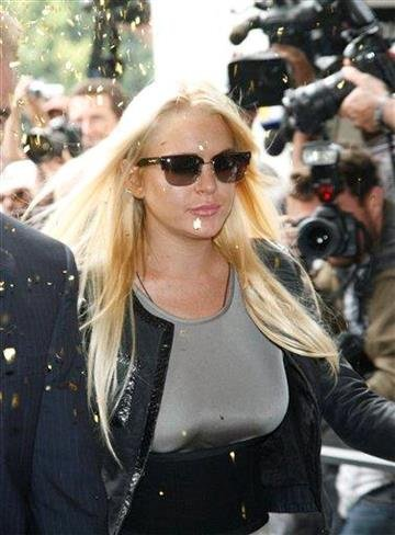 Amid a stream of confetti, actress Lindsay Lohan arrives with an official to court in Beverly Hills, Calif. on Tuesday, July 20, 2010, to begin her 90 day jail sentence for violating the terms of her probation. (AP Photo/Jason Redmond) By Jason Redmond