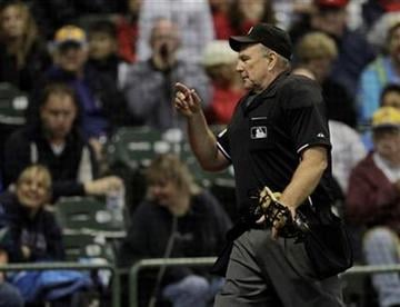 Home plate umpire Bob Davidson throws a fan out of the game during the seventh inning of a baseball game between the Milwaukee Brewers and the St. Louis Cardinals Tuesday, Sept. 7, 2010, in Milwaukee. (AP Photo/Morry Gash) By Morry Gash
