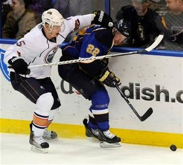 St. Louis Blues' Brad Boyes (22) and Edmonton Oilers' Ladislav Smid (5), of Czech Republic, fight for a loose puck in the second period of an NHL hockey game, Friday, Feb. 4, 2011, in St. Louis. (AP Photo/Bill Boyce) By Bill Boyce