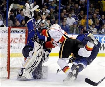 Calgary Flames' Alex Tanguay (40) goes flying into St. Louis Blues goalie Ben Bishop (30) in the first period of an NHL hockey game Tuesday, March 1, 2011 in St. Louis.(AP Photo/Tom Gannam) By Tom Gannam