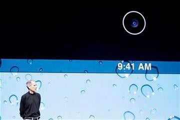 Apple Inc. Chairman and CEO Steve Jobs stands under an image of a camera lens on the new iPad 2 at an Apple event at the Yerba Buena Center for the Arts Theater in San Francisco, Wednesday, March 2, 2011. (AP Photo/Jeff Chiu) By Jeff Chiu