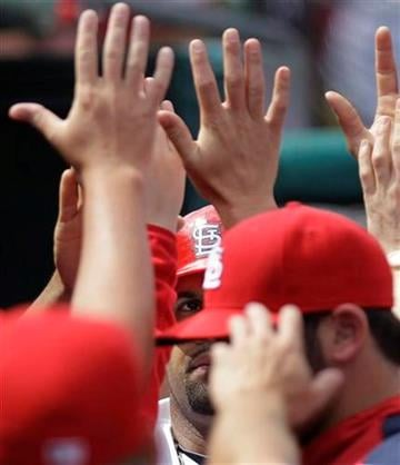 St. Louis Cardinals first baseman Albert Pujols is congratulated by teammates after scoring during a spring training baseball game against the Boston Red Sox, Tuesday, March 8, 2011, in Jupiter, Fla. (AP Photo/Carlos Osorio) By Carlos Osorio