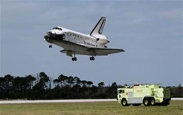 An emergency vehicle stands by near the runway as space shuttle Discovery lands at the Kennedy Space Center in Cape Canaveral, Fla., Wednesday, March 9, 2011. (AP Photo/John Raoux) By John Raoux