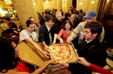 Protesters grab for pizza's at the state Capitol in Madison, Wis., Wednesday, March 9, 2011, after demonstrators retook the Capitol building Wednesday night. (AP Photo/Andy Manis) By Andy Manis