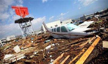 A light plane mingles with debris  following a massive Tsunami triggered by a huge earthquake at Sendai airport in  Sendai, northern Japan,  Saturday, March 12, 2011.(AP Photo/Junji Kurokawa) By Junji Kurokawa