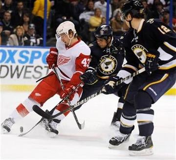 St. Louis Blues' Ryan Reaves, center, and Kevin Shattenkirk (12) battle with Detroit Red Wings' Darren Helm (43) in the first period of an NHL hockey game, Saturday, March 12, 2011, in St. Louis. (AP Photo/Bill Boyce) By Bill Boyce