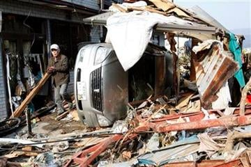 A man walks between a damaged house and car in Ofunato, Iwate Prefecture, northern Japan, Sunday, March 13, 2011, two days after a powerful earthquake-triggered tsunami hit Japan's east coast. (AP Photo/Shizuo Kambayashi) By Shizuo Kambayashi