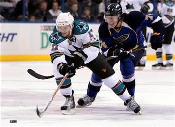 San Jose Sharks' Torrey Mitchell, left, reaches for a loose puck as St. Louis Blues' T.J. Oshie gives chase during the first period of an NHL hockey game Thursday, Nov. 4, 2010, in St. Louis. (AP Photo/Jeff Roberson) By Jeff Roberson