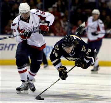 St. Louis Blues' T.J. Oshie, right, goes flying while chasing a loose puck alongside Washington Capitals' Mike Green, left, during the second period of an NHL hockey game Saturday, Feb. 13, 2010, in St. Louis. (AP Photo/Jeff Roberson) By Jeff Roberson