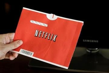 FILE - In this file photo made July 20, 2010, a Netflix customer holds up a movie in Palo Alto, Calif. Netflix Inc. reports quarterly financial earnings Wednesday, Oct. 20, 2010, after the market close. (AP Photo/Paul Sakuma, file) By Paul Sakuma