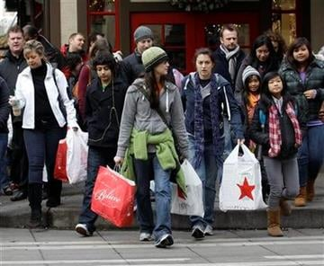 Shoppers carry their bags as they walk in downtown Seattle on Friday, Nov. 26, 2010. (AP Photo/Ted S. Warren) By Ted S. Warren