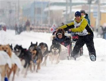 Pat Moon, of Park Ridge, IL.,  rounds a corner during the ceremonial start of the Iditarod Trail Sled Dog Race, Saturday, March 3, 2012 in Archorage, Ak. (AP Photo/Anchorage Daily News, Bob Hallinen) By Bob Hallinen