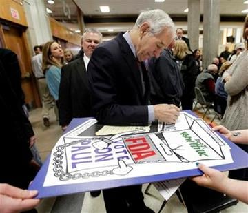 Republican presidential candidate Rep. Ron Paul, R-Texas, autographs a poster at a caucus site at Shawnee Mission Northwest High School  Saturday, March 10, 2012, in Shawnee, Kan. (AP Photo/Charlie Riedel) By Charlie Riedel