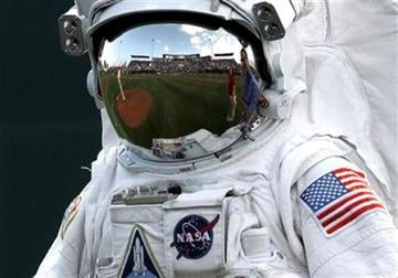 The reflection of Space Coast Stadium is shown in the visor of a NASA space suit prior to  a spring training baseball game between the Washington Nationals and Houston Astros in Viera, Fla.,  Thursday, March 8, 2012. (AP Photo/Paul Sancya) By Paul Sancya