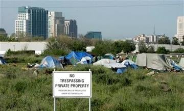 """FILE - In this April 13, 2009 file photo, a """"No trespassing"""" sign is seen at the edge of a homeless camp in Sacramento, Calif.  (AP Photo/Rich Pedroncelli, File) By Rich Pedroncelli"""