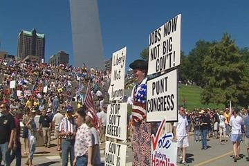 A man dressed in American flag clothes holds a host of signs at the tea party rally. By KMOV Web Producer